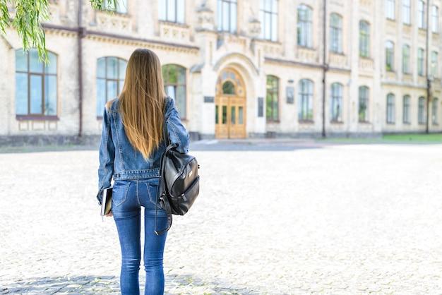 Помощник стажера помогает человеку концепции людей. вид сзади сзади фото портрет серьезного счастливого с длинными волосами в повседневной одежде, смотрящего на дверь на здании размытым фоном
