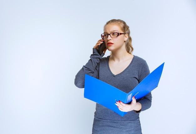 파란색 폴더가있는 어시스턴트가 전화를 걸고 문제가있어 스트레스를받는 것처럼 보입니다.