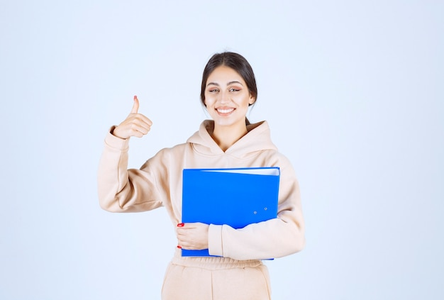 Assistant with a blue folder showing enjoyment sign
