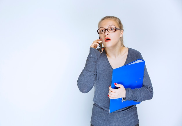 Assistant with a blue folder talking to the phone and looks stressed as something is wrong.