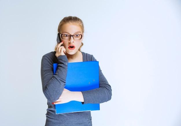 Assistente con una cartella blu che parla al telefono e sembra stressato perché qualcosa non va.