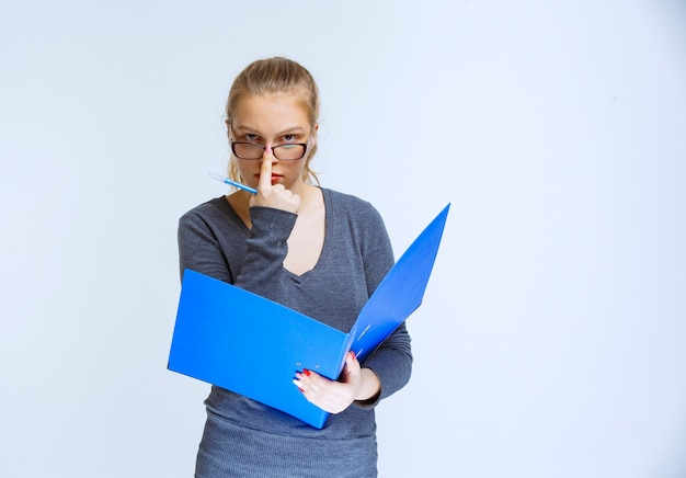 Assistant with eyeglasses checking the blue folder and looks thoughtful and confused.