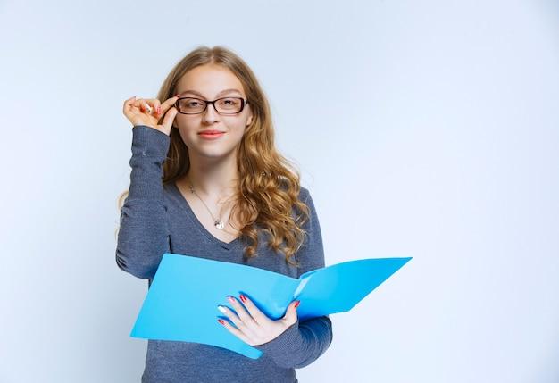 Ассистент в очках держит синюю папку и выглядит так, будто у нее есть блестящая идея или проект ей понравился.