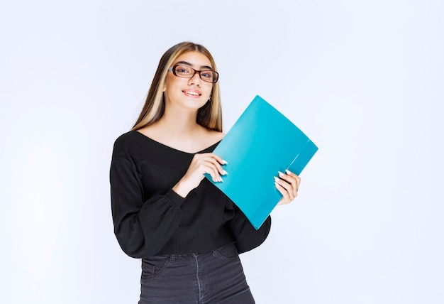Помощник в очках держит синюю папку и улыбается. фото высокого качества