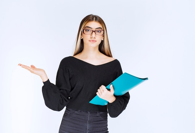 Assistant with eyeglasses holding a blue folder and showing the guests the direction. high quality photo
