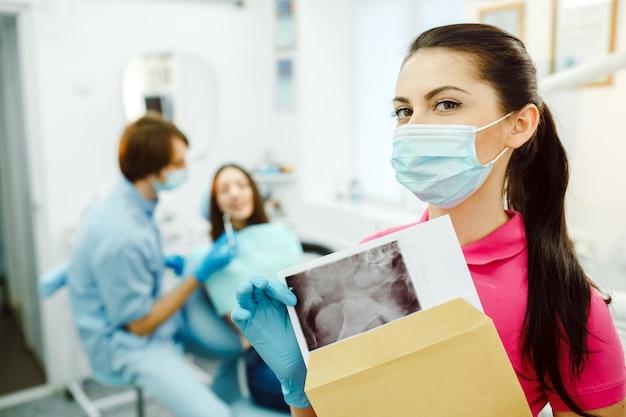 Assistente con maschera mostrando una radiografia