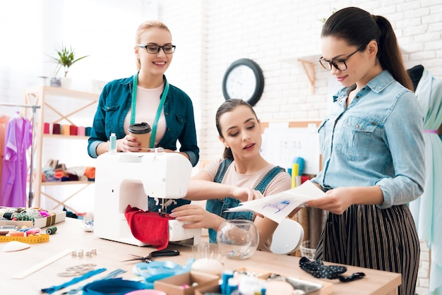 Assistants help to young dressmaker woman.