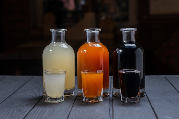 Assorted alcoholic cordials in glasses and decanters on dark wood surface