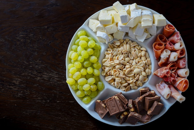 木の上のナッツベーコンチーズチョコレートブドウの上から撮影されたプレート上の盛り合わせ前菜b