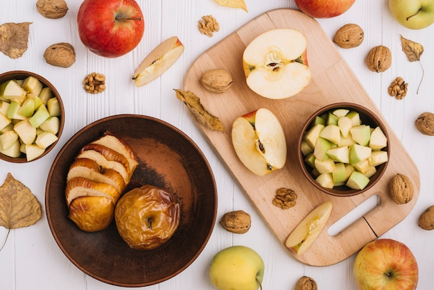 Assorted apples near walnuts and leaves