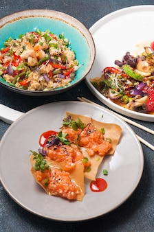 Ассорти из азиатских блюд: рис с креветками, запеченные овощи и чипсы с лососем.