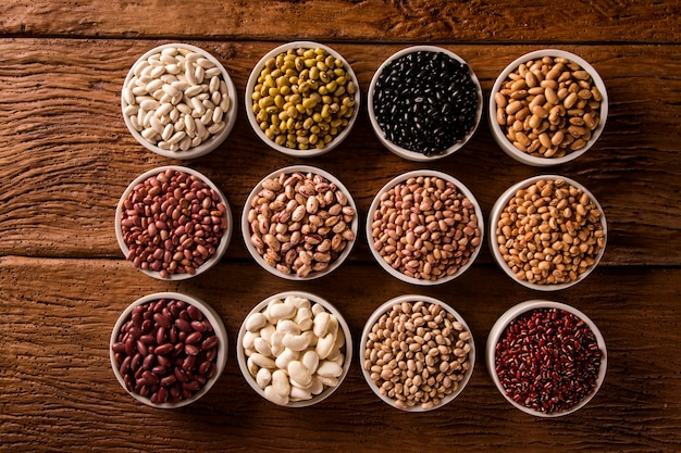 Assorted beans in bowls on wooden table