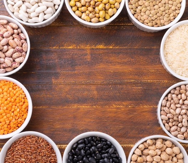 Assorted beans and grains on white bowls with copy space.