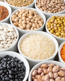 Assorted beans and grains on white bowls.
