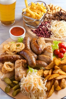 Assorted beer snacks: chicken wings, grilled sausages, potatoes, nuts, cheese, croutons