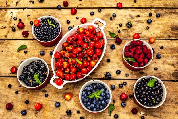 빌베리, 블루 베리, 건포도, 블랙 베리, 체리 및 라즈베리 : 그릇에 모듬 열매. 오래 된 나무 테이블 배경, 평면도