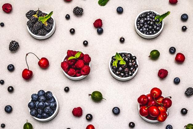 빌베리, 블루 베리, 건포도, 블랙 베리, 체리 및 라즈베리 : 그릇에 모듬 열매. 돌 구체적인 배경, 평면도