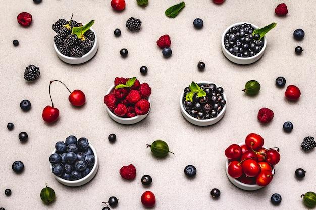 빌베리, 블루 베리, 건포도, 블랙 베리, 체리 및 라즈베리 : 그릇에 모듬 열매. 돌 구체적인 배경