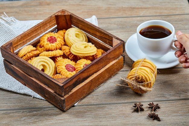Ассорти из печенья и чашка кофе на деревянном столе.