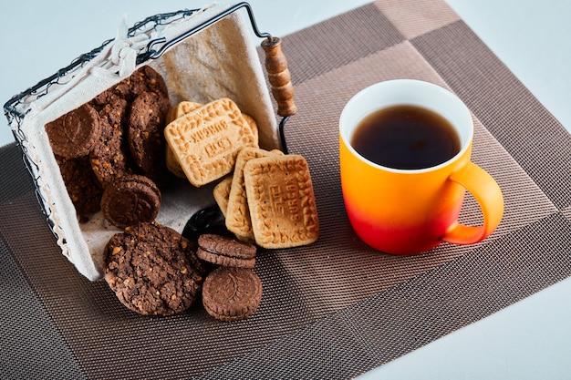 灰色の表面に各種ビスケット、キャンディー、お茶。