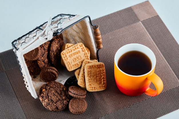 Biscotti assortiti, caramelle e una tazza di tè sulla superficie grigia.