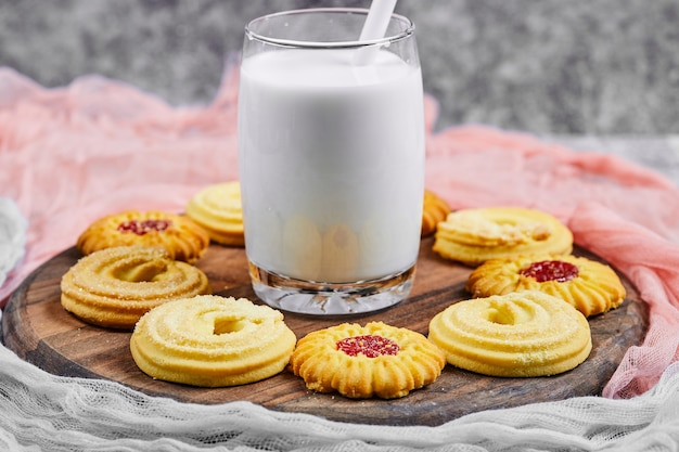 Assorted biscuits and a glass of milk on a wooden plate.