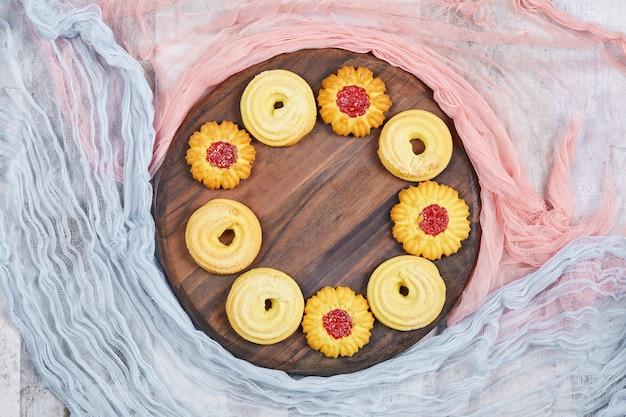 Ассорти из печенья на деревянной тарелке с розовыми и синими скатертями. фото высокого качества