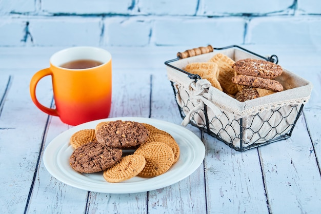 Assorted biscuits in plate and basket and a cup on blue table.