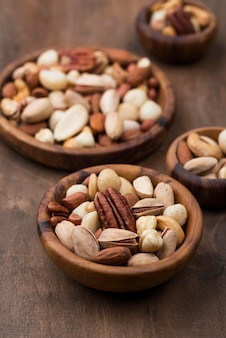 Assorted bowls of delicious nuts snack high view