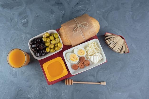 Ассорти из блюд на завтрак наверху книги, рядом с небольшой записной книжкой, ложкой меда и стаканом сока на мраморном столе.
