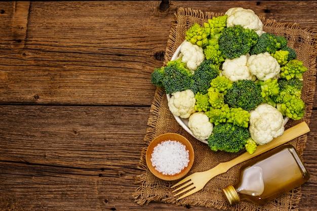 모듬 브로콜리, romanesco 및 콜리 플라워. 건강 식품을위한 신선한 익은 성분. 오래 된 나무 보드 배경, 평면도