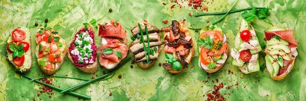 Assorted bruschetta with various toppings.appetizing bruschetta.variety of small sandwiches.mix bruschetta