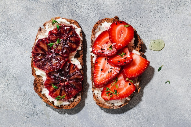 Assorted bruschetta with whole grain bread, cottage cheese, blood orange, strawberry, thyme