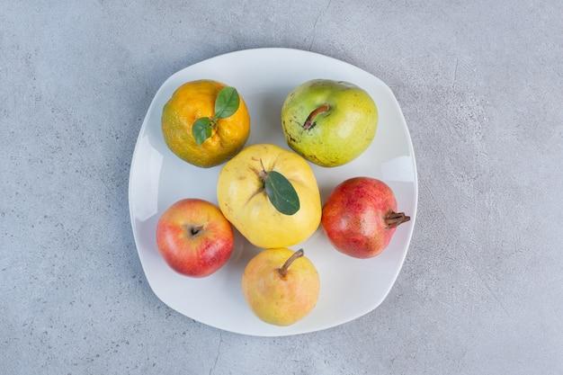 Fascio assortito di melograno, pere, mandarino, mela cotogna e mela su un piatto su fondo di marmo.