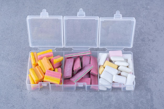Assorted bundles of bubblegums neatly piled in small containers on marble surface