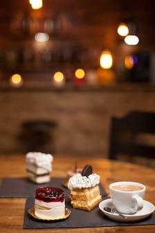 コーヒーショップの木製テーブルの上にデザート用の各種ケーキ。天然素材のケーキ。おいしい一杯のコーヒー。さまざまなフレーバーのケーキ。