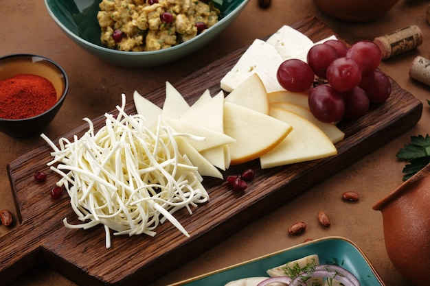 Assorted caucasian cheeses are neatly laid out on a wooden board cheese plate in a georgian