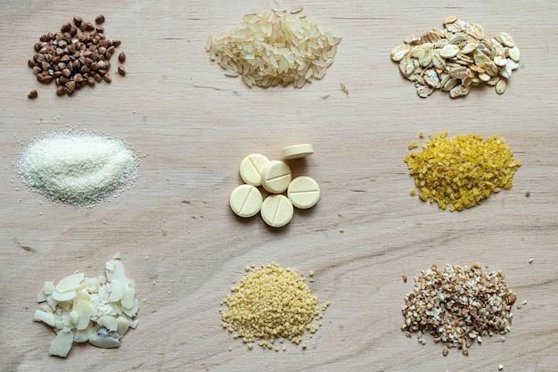 Ассорти из семян каши из злаков на деревянном фоне: гречка, рис, манная крупа, пшеница, кускус, овсянка