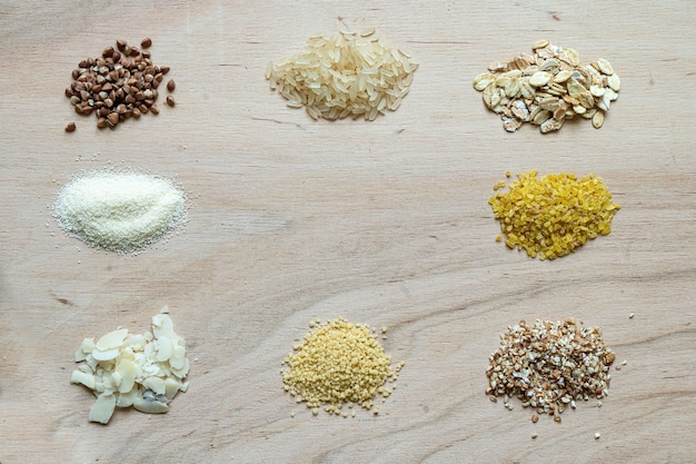 Assorted cereal grain porridge seeds set on a wooden background: buckwheat, rice, semolina, wheat, couscous, oatmeal