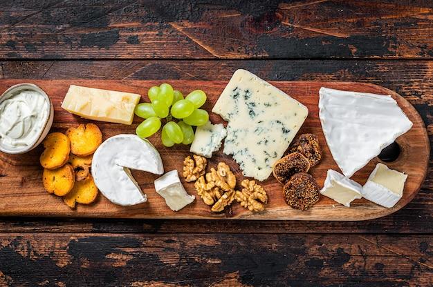 브리, 카망베르, 로크 포르, 파마산 치즈, 블루 크림 치즈, 포도, 견과류가 들어간 모듬 치즈 보드. 어두운 나무 배경입니다. 평면도.