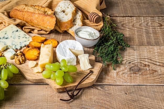 Сырное ассорти бри, камамбер, рокфор, пармезан, голубой сливочный сыр с виноградом, инжиром, хлебом и орехами. деревянный фон. вид сверху. скопируйте пространство.