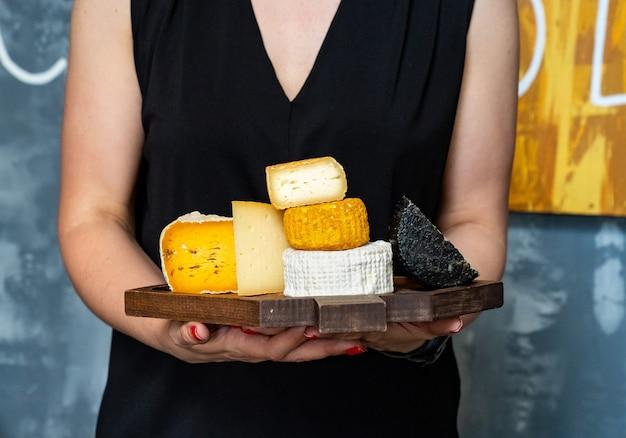 Ассорти из сырных головок на разделочной доске в руках женщины. сыроварня и сырный цех. натуральные фермерские молочные продукты. реклама и меню.