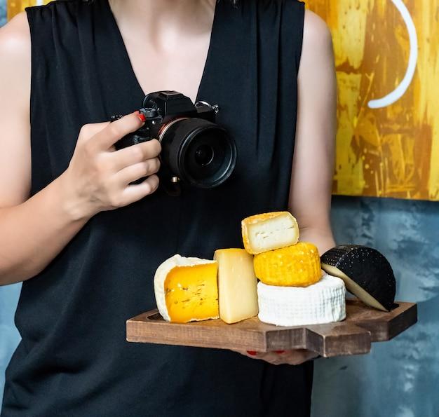 Ассорти из сырных головок на разделочной доске в руках женщины с фотоаппаратом. сыроварня и сырный цех. натуральные фермерские молочные продукты. реклама и меню.