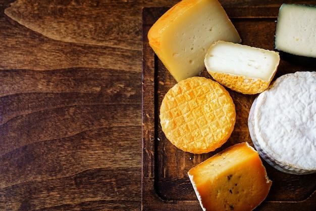 Ассорти из сырных головок на разделочной доске на деревянном столе. сыроварня и сырный цех. натуральные фермерские молочные продукты. реклама и меню. копировать пространство