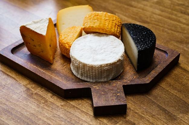 Ассорти из сырных головок на разделочной доске на деревянном столе. сыроварня и сырный цех. натуральные фермерские молочные продукты. реклама и меню.