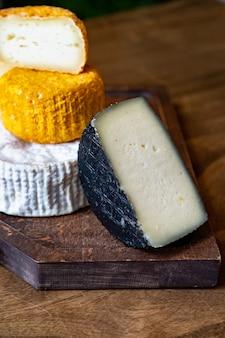 나무 테이블에 커팅 보드에 모듬된 치즈 머리. 치즈 공장과 치즈 가게. 천연 농장 유제품. 광고 및 메뉴.