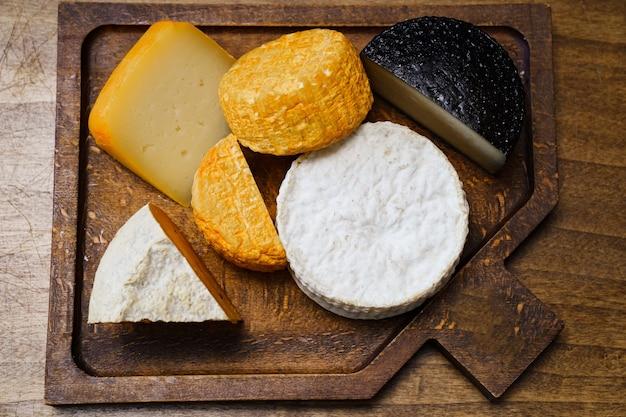 Ассорти из сырных головок на разделочной доске на деревянном столе. сыроварня и сырный цех.