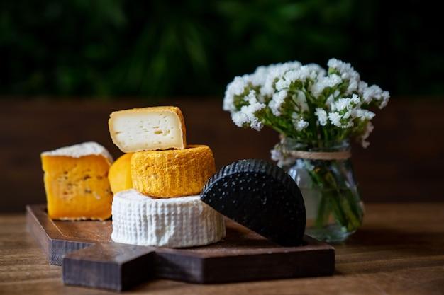 Ассорти сырных головок на разделочной доске на деревянном столе с небольшим букетом цветов. сыроварня и сырный цех. натуральные фермерские молочные продукты. реклама и меню.