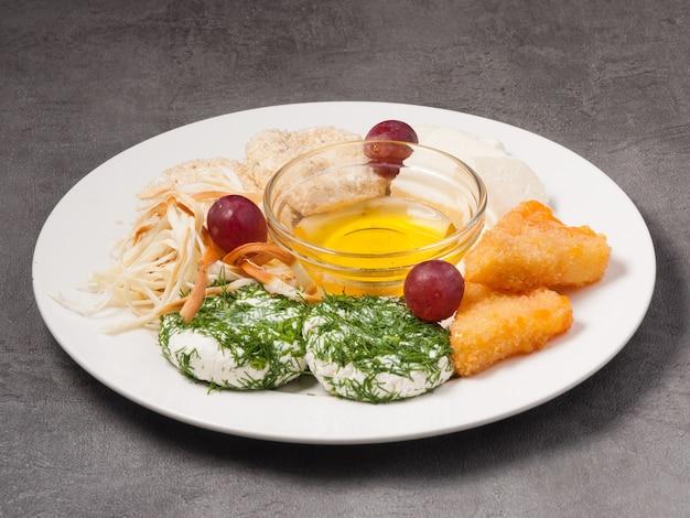白い皿に蜂蜜とレストランで盛り合わせチーズ