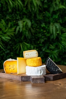 나무 테이블에 커팅 보드에 모듬된 치즈. 치즈 공장과 치즈 가게. 천연 농장 유제품. 광고 및 메뉴.